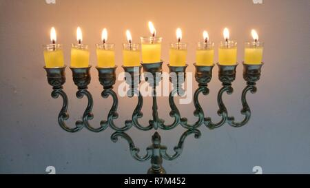 Vintage oil chanukiah - traditional Jewish candelabrum with nine candles burning during the holiday of Chanukah. Hanukkah, Hanukah concept image. - Stock Image