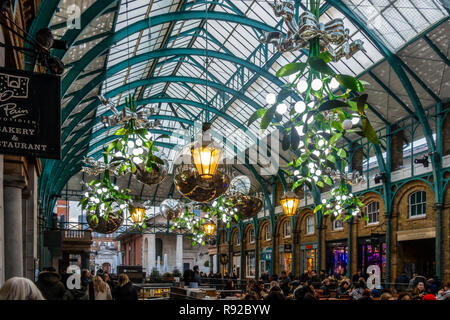 Christmas decorations of giant mistletoe, silver baubles and old-fashioned lamps suspended from the ceiling of Covent Garden Market piazza. - Stock Image