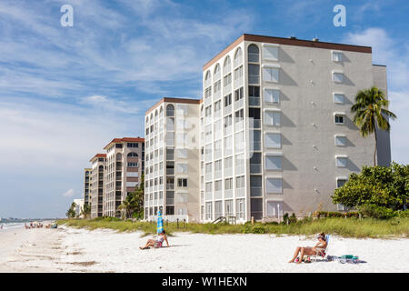 Florida Bonita Springs Gulf of Mexico public beach Little Hickory Beach oceanfront condominium building prime real estate woman - Stock Image