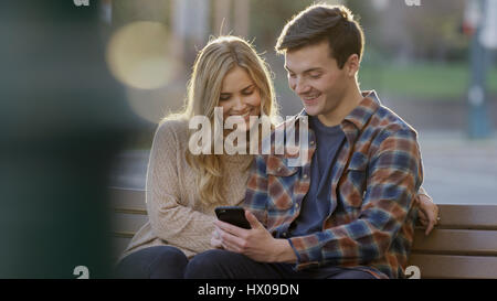 Selective focus view of smiling boyfriend and girlfriend sharing smartphone and sitting on bench - Stock Image