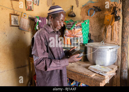 Samba village, Yako Province, Burkina Faso: Listening to an educational radio programme on nutrition and food security  being broadcast by Natigmbzanga Radio. - Stock Image