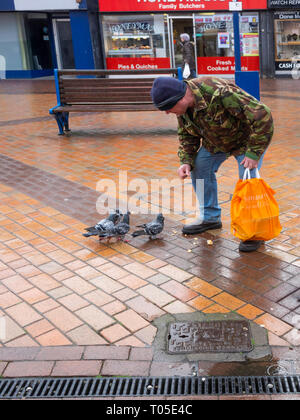 A man in a camouflage jacket in Redcar Town centre feeding pigeons in defiance of local by-laws forbidding this practice. - Stock Image