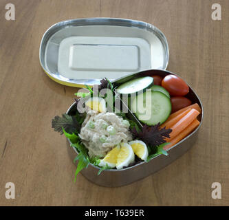 Stainless steel lunchbox divided to two compartments filled with healthy snacks - Stock Image