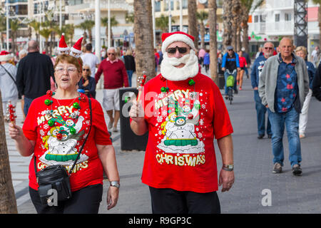 Benidorm, Costa Blanca, Spain, 25th December 2018. British tourists dress for the occasion on Christmas Day in this favourite getaway destination for Brits escaping the cold weather at home. Temperatures will be in the mid to high 20's Celsius today in this mediterranean hotspot. Couple wearing Christmas clothing and santa hats. Middle aged couple wearing bright red Christmas jumpers and hats, with santa beard waliking outside in sun. - Stock Image