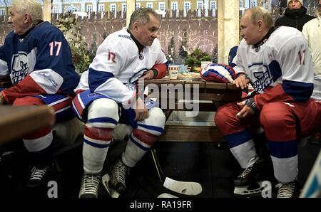 Moscow, Russia. 29th December 2018. Russian President Vladimir Putin, right, chats with Defense Minister Sergei Shoigu following the Night Hockey League match in the rink at the GUM Department store in Red Square December 29, 2018 in Moscow, Russia. Credit: Planetpix/Alamy Live News - Stock Image