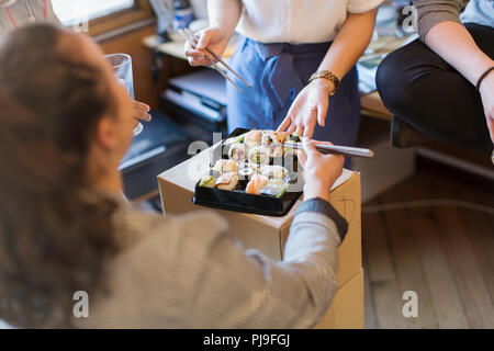 Business people eating sushi in office - Stock Image