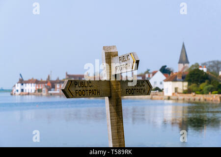 Public footpath signpost on path around Bosham Creek at high tide in Chichester harbour. Bosham, Chichester, West Sussex, England, UK, Britain - Stock Image