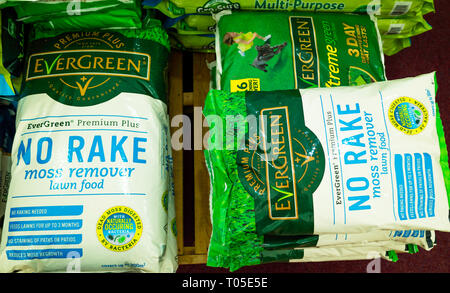 A stack of bags of Aftercut lawn feed weed and moss killer in a garden centre - Stock Image