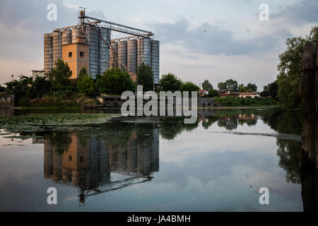 Old factory with silos and reflection on the water - landscape - Stock Image