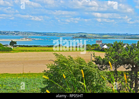 A rural view over French farming land near St Pol de Leon,with the seaside resort of Carantec visible across the bay.The campsite is Camping Trologot. - Stock Image