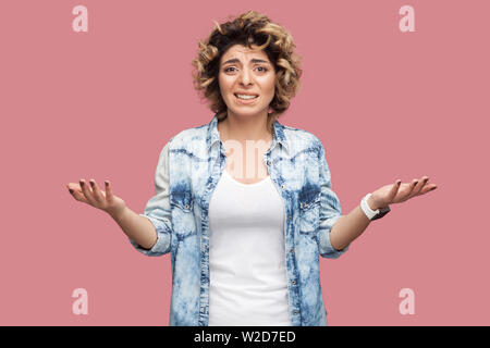 What? Portrait of confused or shocked young woman with curly hairstyle in casual blue shirt standing with raised arms and looking at camera worried. i - Stock Image