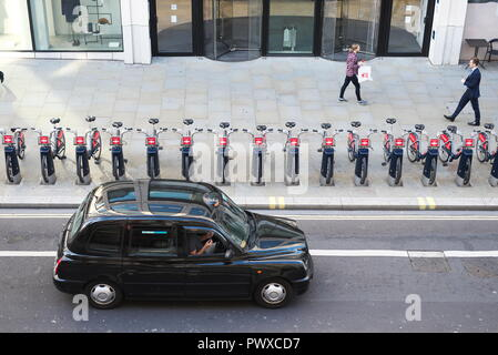 drone aerial photos of london black cab travels along a major A road in the city of London, with TFL boris Bikes/rent bikes racked up outside offices - Stock Image