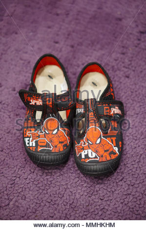 Pair of child shoes with Spiderman illustration on the floor - Stock Image