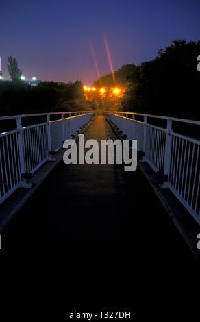 dark and eerie floodlit footbridge - Stock Image
