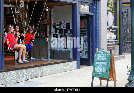 Elsewhere living museum in Greensboro North Carolina. Girls on swings in the window of the museum. - Stock Image