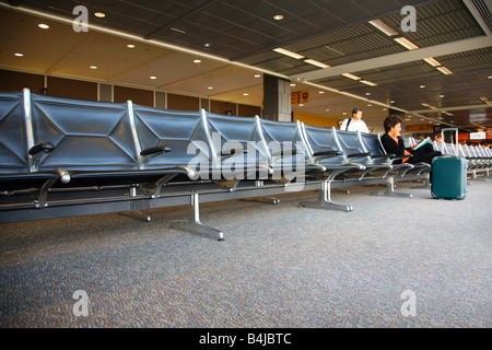 Woman reading at a mostly empty airport gate, Austin-Bergstrom International Airport - Stock Image