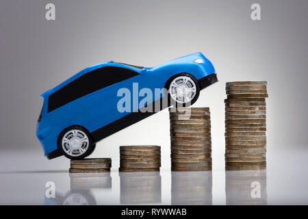 Close-up Of A Blue Car Over Rising Golden Stacked Coins - Stock Image