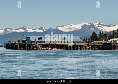 A cannery on the tiny village of Petersburg on Mitkof Island along the Wrangell Narrows in Frederick Sound with the Alaska Coast Range of mountains behind on Mitkof Island, Alaska. Petersburg settled by Norwegian immigrant Peter Buschmann is known as Little Norway due to the high percentage of people of Scandinavian origin. - Stock Image