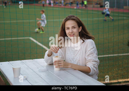 High school student drinking coffee on summer terrace of school cafe. She is smiling and posing for camera. Football field in the background. Time for - Stock Image