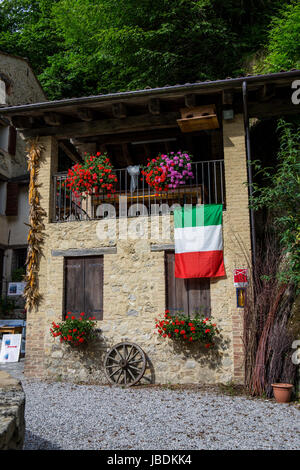 A cottage with colorful flowers and italian flag - Stock Image