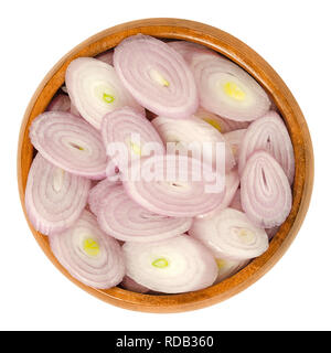 Sliced shallots in wooden bowl. Chopped. Rings. Type of onion and variety of Allium cepa. Purple, edible, raw, organic, vegan, plant. - Stock Image