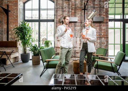 Young couple dressed in white standing together with drinks during the conversation in the beautiful spacious loft interior - Stock Image