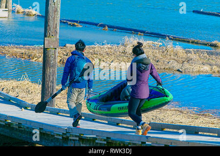 Young Asian couple carrying an inflatable kayak along a wooden ramp. Grant Narrows Regional Park, Pitt Meadows, British Columbia, Canada - Stock Image
