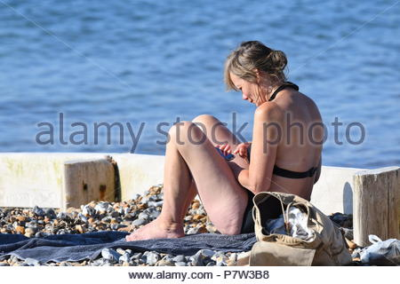 Worthing, UK. Sunday 8th July 2018. A woman sits on the beach early today on a very warm morning in Worthing, on the South Coast. Credit: Geoff Smith / Alamy Live News. - Stock Image