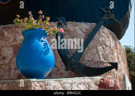 Large anchor and blue urn with geraniums - Stock Image