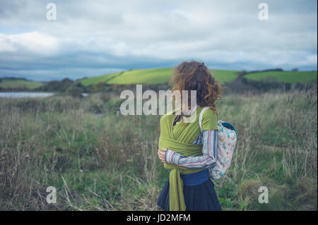A young mother is walking in the countryside with her baby in a sling - Stock Image