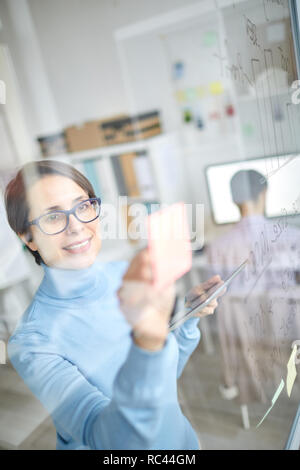 Pretty casual businesswoman standing by transparent board and reading workflow notes in office - Stock Image