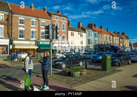 The High Street of the market town of Stokesley North Yorkshire on a sunny Autumn day ladies chatting by the road pedestrian crossing - Stock Image