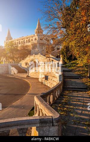 Budapest, Hungary - Sunrise at the entrance of Fisherman's Bastion (Halaszbastya) with autumn foliage, sunshine and clear blue sky - Stock Image