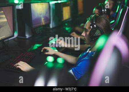 Group of serious young men in headsets sitting in line and using computers while playing pc games in computer club - Stock Image