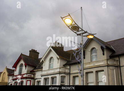 Modern street lighting switched on in late afternoon in mid December in Newcastle County Down Northern Ireland - Stock Image