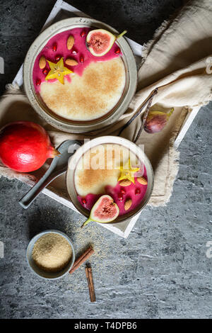 Semolina pudding with homemade pomegranate syrup, decorated with star fruit, figs and almonds - Stock Image