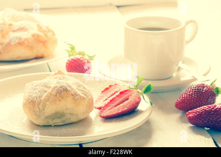 Fluffy strawberry pastry with coffee and whole strawberry on an old wooden table. - Stock Image