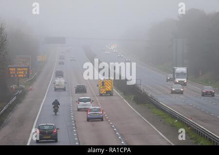 Ashford, Kent, UK. 30 Dec, 2018. UK Weather: A foggy morning on the M20 motorway in  Ashford, Kent. An ambulance with lights flashing heads towards Dover. © Paul Lawrenson 2018, Photo Credit: Paul Lawrenson / Alamy Live News - Stock Image
