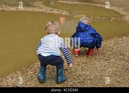 Two children before jumping into a puddle at Blashford Lakes Nature Reserve. - Stock Image