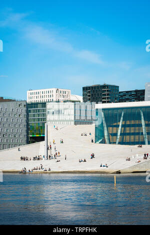 Oslo Opera House, view across the fjord of people on the vast access ramp leading to the roof of the Oslo Opera House, with Barcode Buildings beyond. - Stock Image