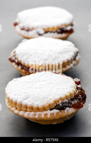 Three mince pies dusted with icing sugar - Stock Image