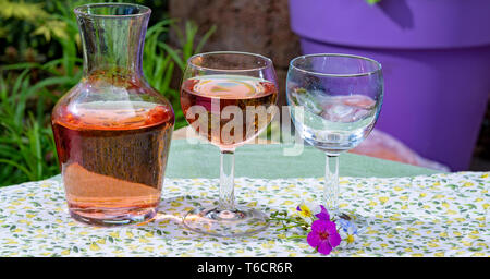 Wine carafe and glasses with cold rose wine and wild flowers in summer sunny day in garden - Stock Image