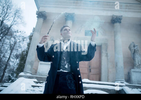 Young man in image of black magician makes a spell with the help of magic wand and smoke. - Stock Image