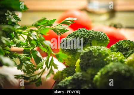 Parsley and broccoli with tomatoes in the background - Stock Image