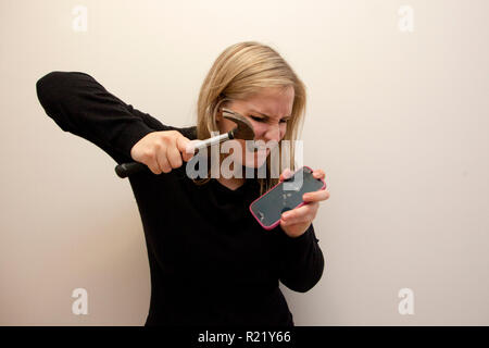 An angry woman takes a hammer and smashes her cell phone - Stock Image