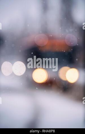 Defocused view of traffic driving through winter snow - Stock Image