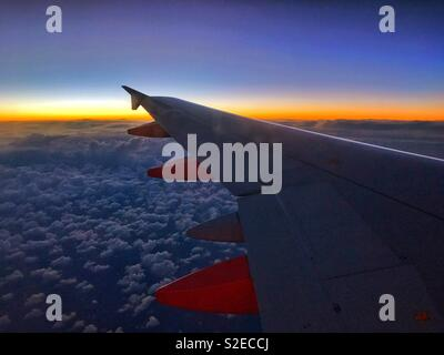 Above the clouds after the sun has disappeared below the horizon. The view from an EasyJet aircraft window as it returns to the United Kingdom on the last flight of the day. Photo © COLIN HOSKINS. - Stock Image