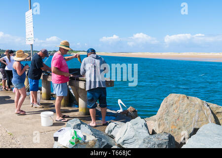 Crowdy Head, NSW, Australia-April 21, 2019: Fishermans cleaning fish in the small fishing village of Crowdy Head, famous for the breakwall used as a s - Stock Image