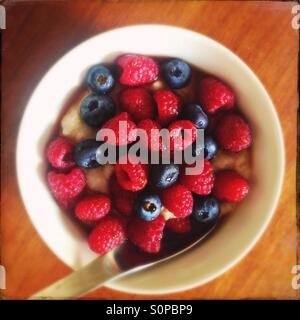 Porridge with raspberries and blueberries with maple syrup for breakfast - Stock Image