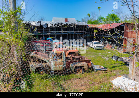 LIMESTONE, TN, USA-4/27/19:  A fenced yard containing junked antique trucks and cars, and a dilapidated building. - Stock Image